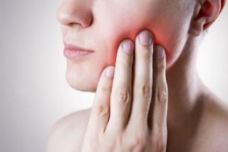 Woman touching her cheek in pain