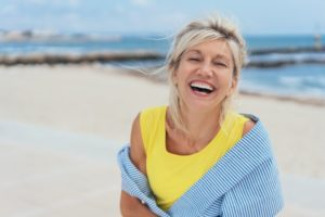 woman smiling with implants at the beach